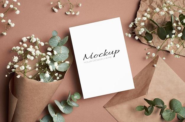 Makieta karty z pozdrowieniami lub zaproszeniem z kopertą, kwiatami hipsofili i eukaliptusa