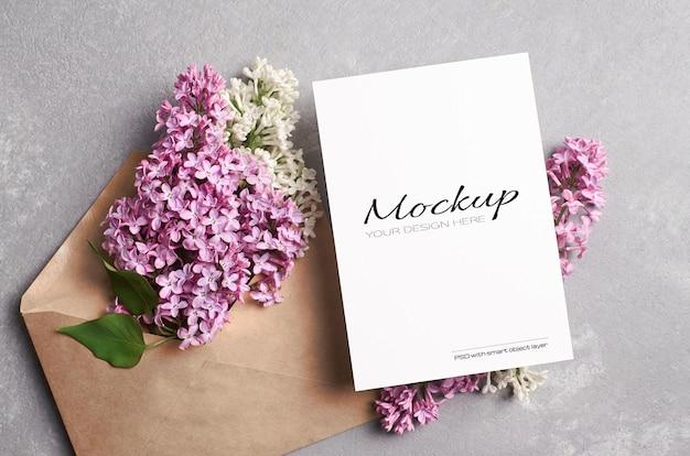 Makieta karty z pozdrowieniami lub zaproszeniem z kopertą z kwiatami bzu