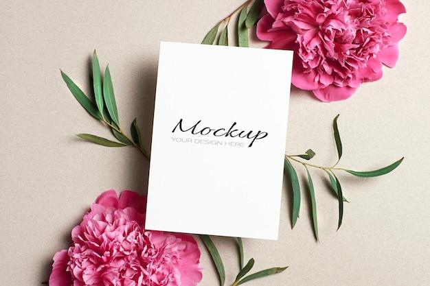 Makieta karty z pozdrowieniami lub zaproszeniem z różowymi kwiatami piwonii i gałązkami eukaliptusa