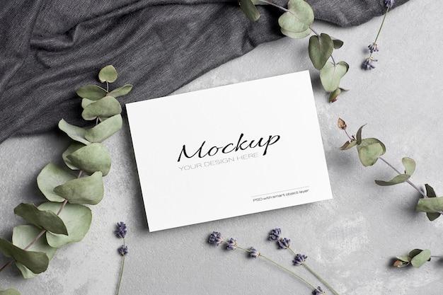 Makieta karty z pozdrowieniami lub zaproszeniem z suchymi kwiatami lawendy i gałązkami eukaliptusa