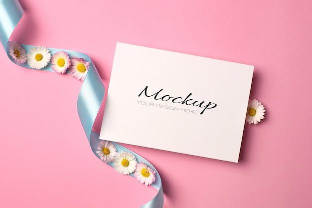 Makieta karty z pozdrowieniami lub zaproszeniem z turkusową wstążką i stokrotkami na różowo