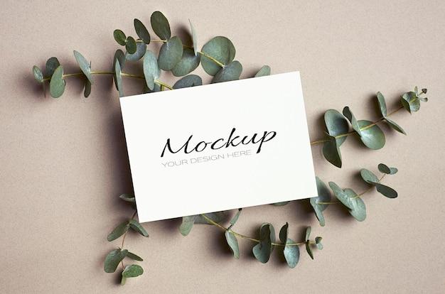 Makieta karty z pozdrowieniami lub zaproszeniem z zielonymi gałązkami eukaliptusa