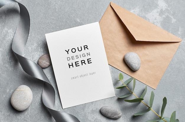Makieta karty z pozdrowieniami z kopertą, gałązką eukaliptusa i szarymi kamieniami
