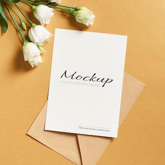 Makieta karty z pozdrowieniami z kopertą i białymi kwiatami eustoma na złocie
