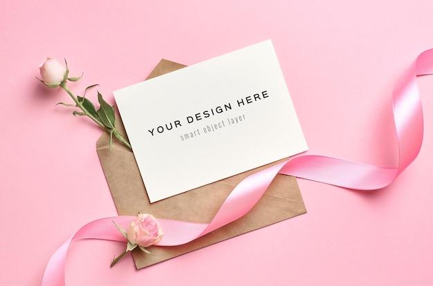 Makieta karty z pozdrowieniami z kopertą, kwiatami róż i różową wstążką