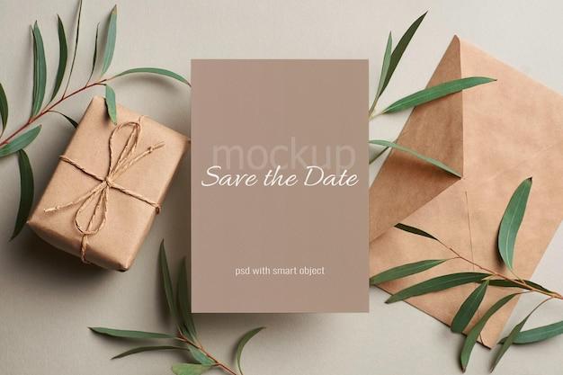 Makieta karty zaproszenia ślubne z kopertą, pudełkiem prezentowym i gałązkami eukaliptusa