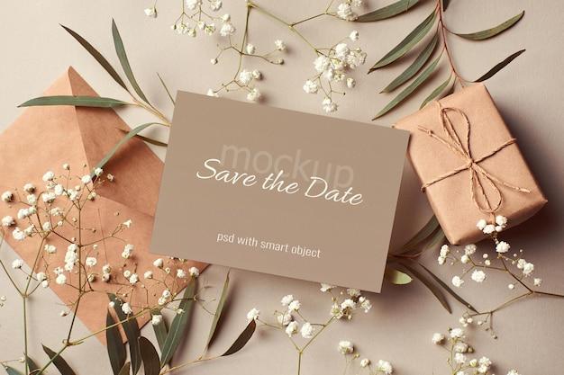 Makieta karty zaproszenia ślubne z kopertą, pudełkiem prezentowym oraz gałązkami eukaliptusa i hipsofili