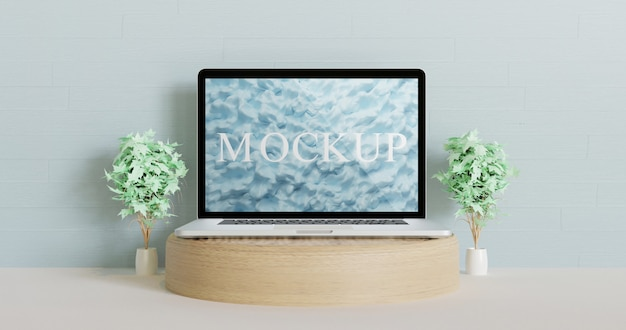 Makieta laptopa na drewnianym podium przed niebieską ścianą