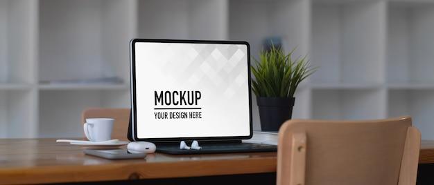 Makieta laptopa na drewnianym stole w wspólnej przestrzeni roboczej