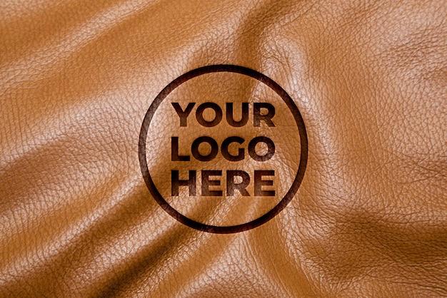 Makieta logo efekt grawerowania na skórzanej teksturze tła
