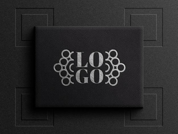 Makieta logo na czarnym skórzanym pudełku z efektem wytłoczenia
