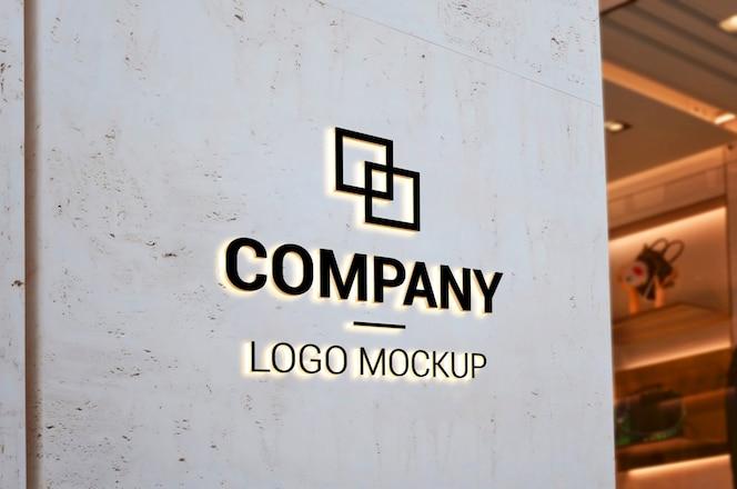 Makieta logo na pustej ścianie wejściowej światłem. branding