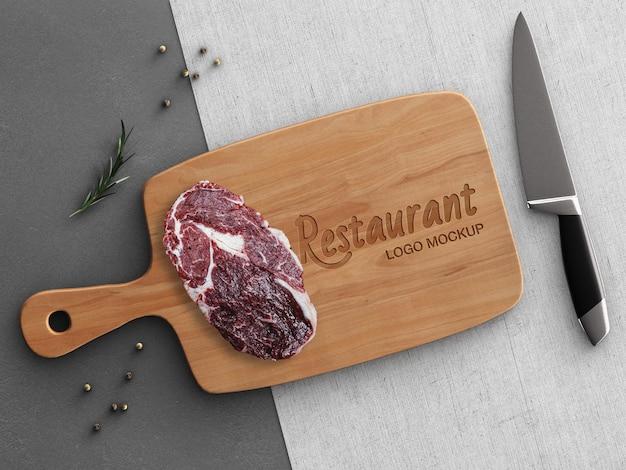 Makieta logo restauracji koncepcja gotowania z drewnianą deską do krojenia stekiem na białym tle dekoracji kuchni