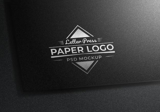 Makieta logo srebrny naciśnij list na czarnym papierze z teksturą
