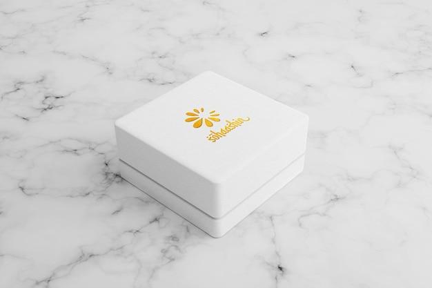 Makieta logo złotej folii na białym kwadratowym pudełku z biżuterią