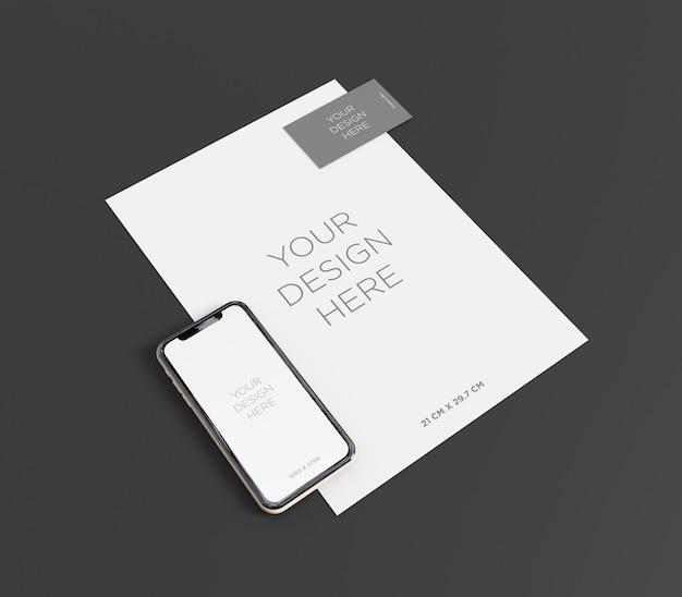 Makieta marki ze smartfonem, wizytówką i widokiem perspektywicznym papieru a4