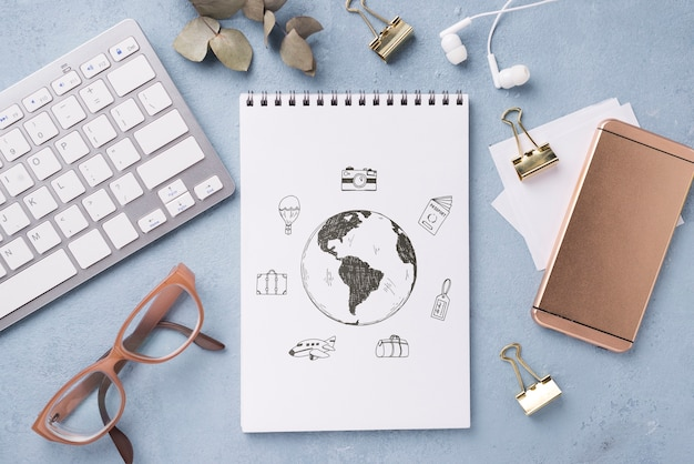 Makieta notebooka i artykuły papiernicze leżące na płasko w pobliżu okularów i klawiatury