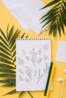 Makieta notesu i długopis leżący na płasko w pobliżu z tropikalnymi liśćmi