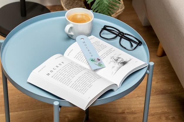 Makieta otwartej książki pod wysokim kątem na stoliku do kawy z zakładką