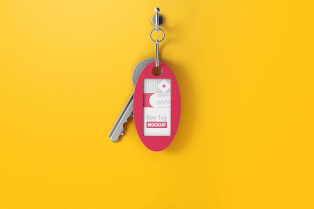 Makieta owalnego breloczka z kluczem na haku ściennym