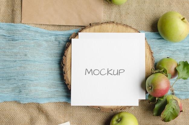 Makieta papeterii letniej z życzeniami lub zaproszenie na ślub z jabłkami, niebieskim bieżnikiem, na beżowej przestrzeni w stylu rustykalnym i naturalnym