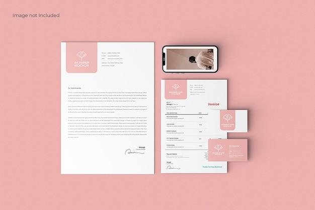 Makieta papeterii nowoczesnej firmy na różowym stole, widok z góry