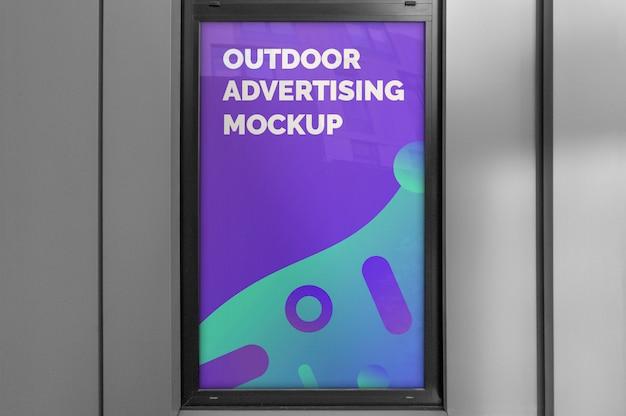 Makieta pionowej reklamy zewnętrznej w oknie z czarną ramą na szarej fasadzie