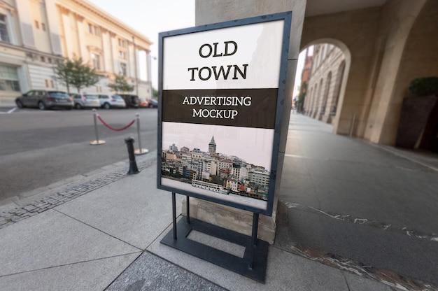 Makieta pionowej, zewnętrznej, czarnej, metalicznej ramy reklamowej stoi na chodniku starego miasta
