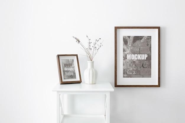 Makieta pionowych ramek na białej ścianie i meblach z suchymi roślinami w wazonie