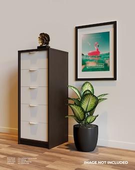 Makieta plakatu z ramą artystyczną obok szafki nad roślinami