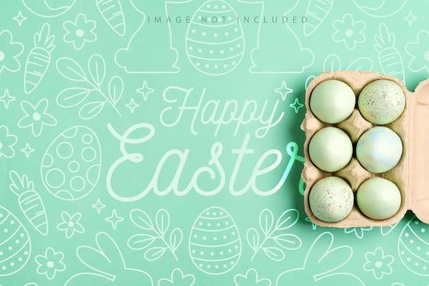 Makieta pocztówka z papierowym pojemnikiem z pomalowanymi na zielono jajkami na zielonej powierzchni, koncepcja wesołych świąt.
