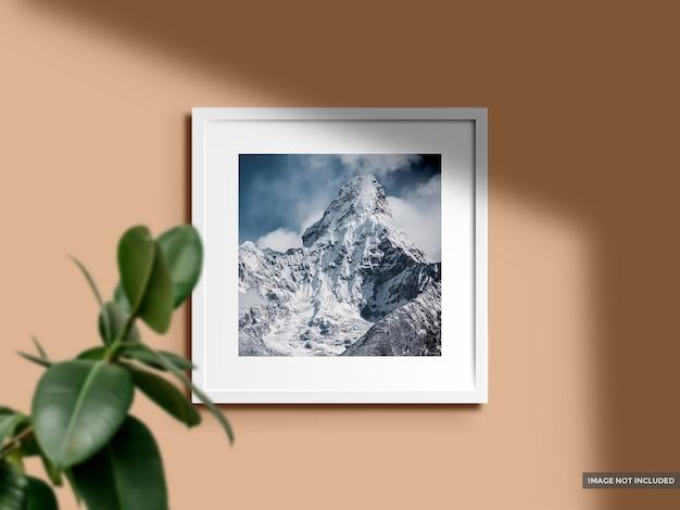 Makieta pustej ramki na zdjęcia w kolorowej ścianie