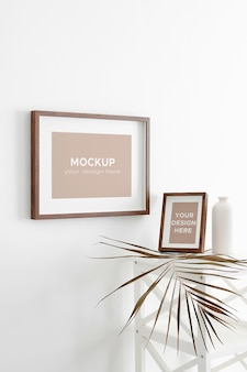 Makieta ramek do zdjęć lub grafiki na białej ścianie z dekoracjami suchych liści palmowych w wazonie