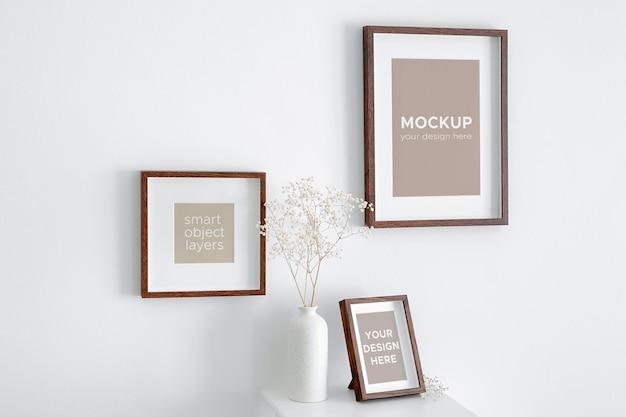 Makieta ramek do zdjęć lub grafiki na białej ścianie z dekoracjami suchych roślin gipsówki