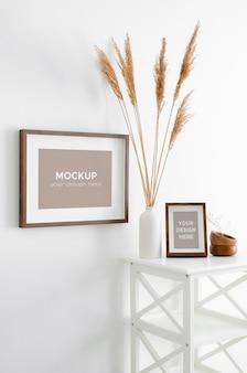 Makieta ramek do zdjęć lub grafiki na białej ścianie z dekoracjami suchych roślin w wazonie