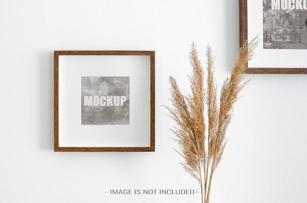 Makieta ramek do zdjęć na białej ścianie z suchymi dekoracjami roślinnymi
