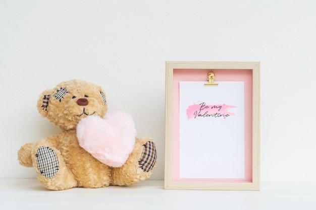 Makieta ramka na zdjęcia i słodki miś z różowym sercem.