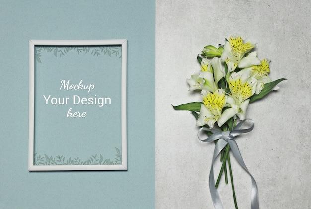 Makieta ramka na zdjęcia z kwiatami i wstążki na szarym niebieskim tle