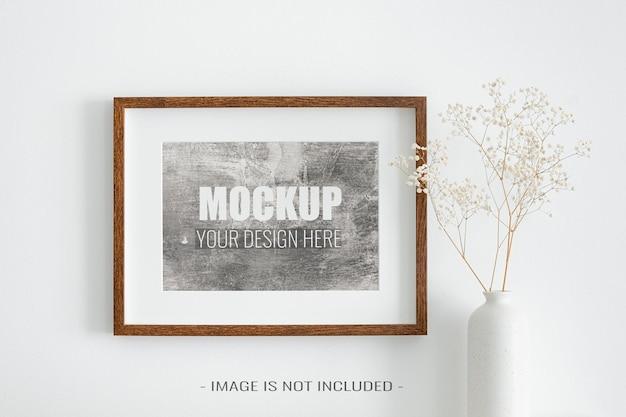 Makieta ramki do zdjęć krajobrazowych na białej ścianie z dekoracjami suchej gipsówki