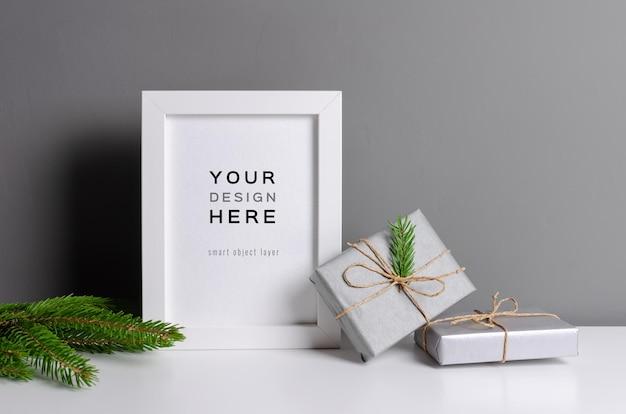 Makieta ramki do zdjęć lub grafiki z pudełkami na prezenty świąteczne i zieloną gałęzią jodły