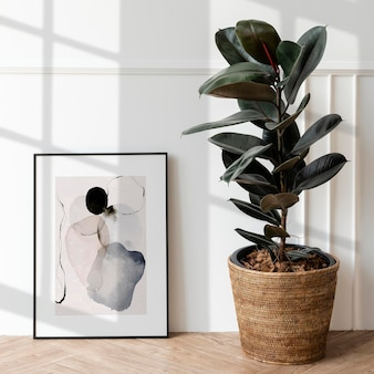 Makieta ramki na zdjęcia przez gumową roślinę na drewnianej podłodze