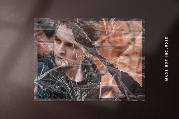 Makieta ramki na zdjęcia w rozdartej fakturze papieru i plastikowym opakowaniu
