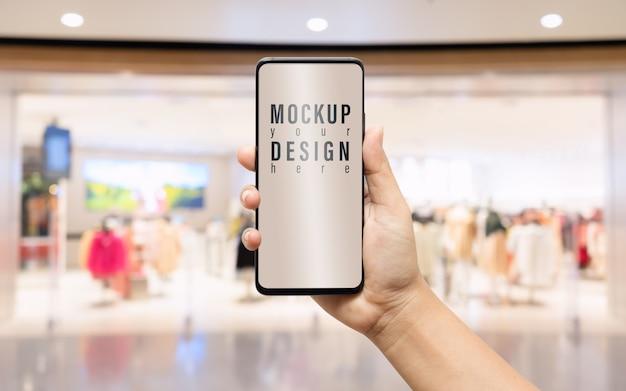 Makieta ręki trzymającej smartphone wirh rozmyte sklep odzieżowy tło