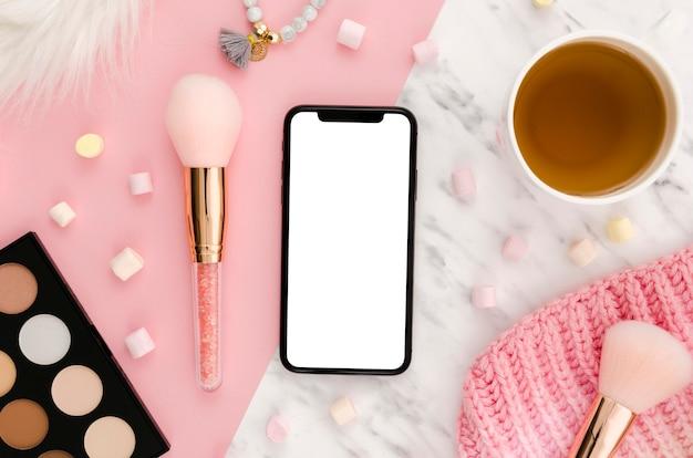 Makieta smartfona leżącego na płasko z paletą makijażu i kawą na biurku