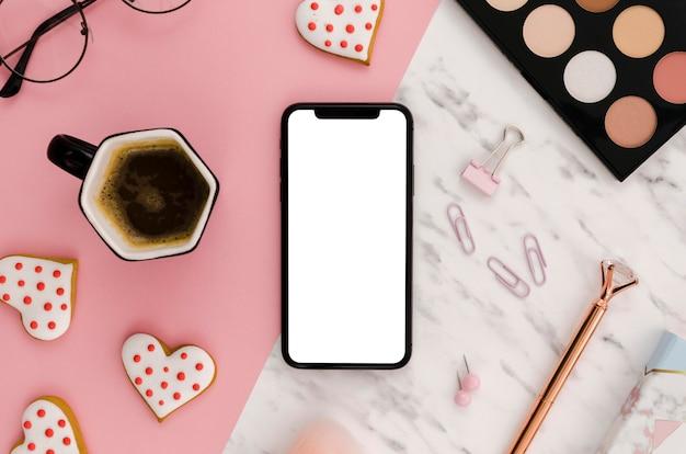 Makieta smartfona leżącego na płasko z paletą makijażu i kawą