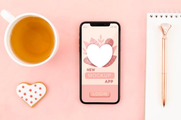 Makieta smartfona leżącego płasko z ciasteczkiem i kawą