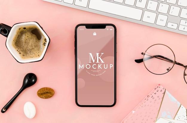 Makieta smartfona leżącego płasko z kawą i szklankami