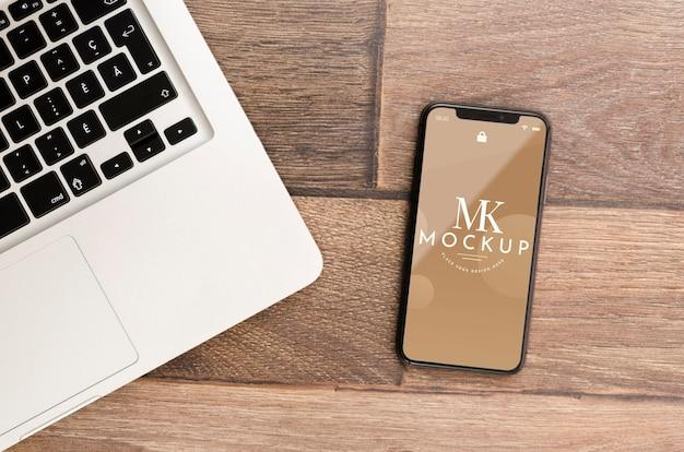 Makieta smartfona leżącego płasko z laptopem na biurku