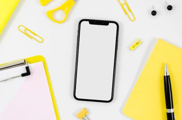 Makieta smartfona leżącego płasko z papeterią na biurku