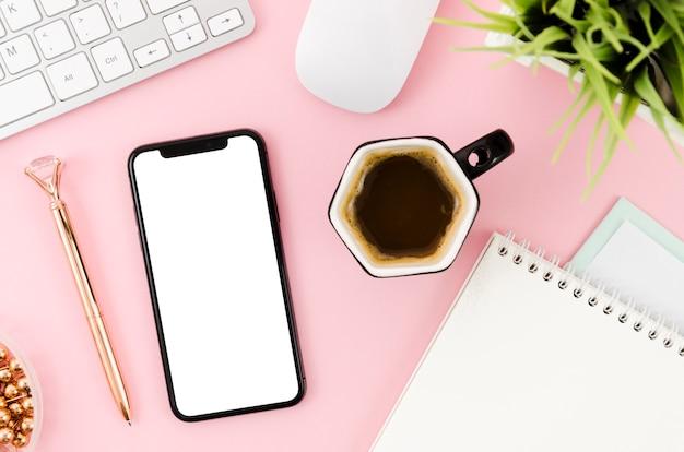 Makieta smartfona leżącego płasko ze schowkiem i kawą